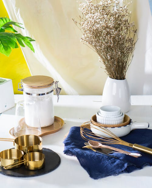 Kitchen utensils and dishware with plant in vase on table