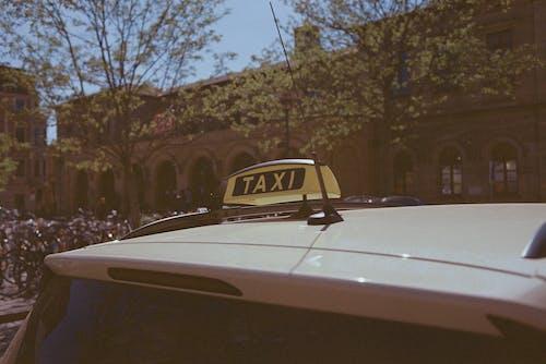 White Car Near Brown Building
