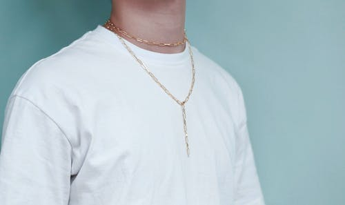 Crop unrecognizable male in white crumpled wear and golden chain on neck near wall