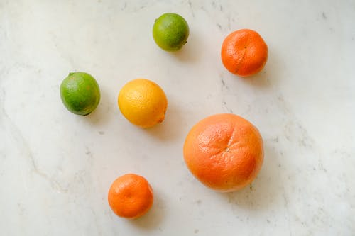 Top view of fresh whole grapefruit lemon tangerines and limes placed on marble surface