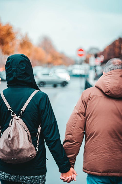 Back view of crop anonymous gray haired man holding by hand girlfriend with backpack on street in autumn town