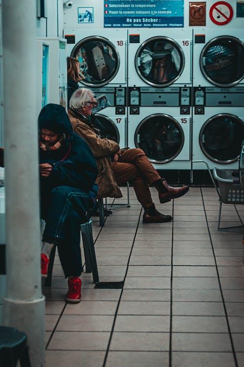 Anonymous people sitting near washing machines in laundromat