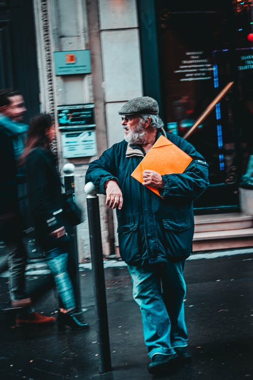 From above of bearded elderly male in casual wear and felt cap with colorful file standing leaned on fence on city street while looking away
