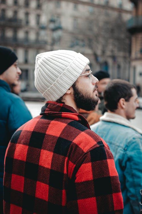 Trendy ethnic tourist in plaid coat on city street