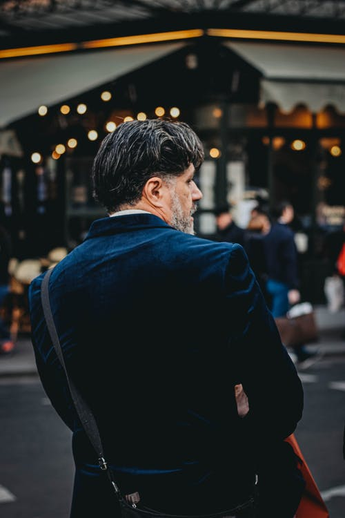 Unrecognizable stylish mature ethnic man near road in city