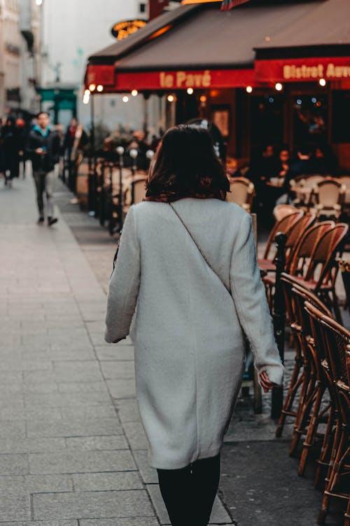Woman in warm coat walking along crowded street