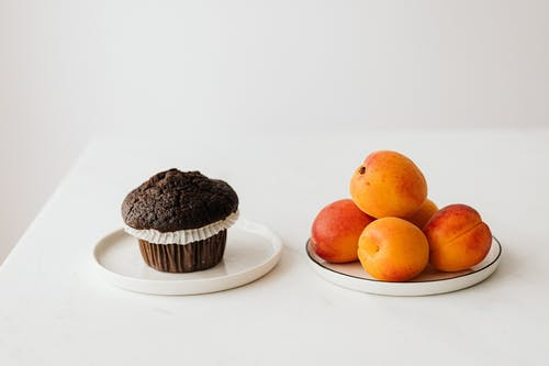 Fresh ripe apricots served on table with chocolate muffin