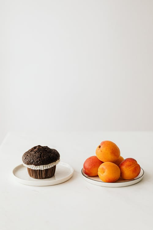 Chocolate muffin and fresh organic apricots placed on table