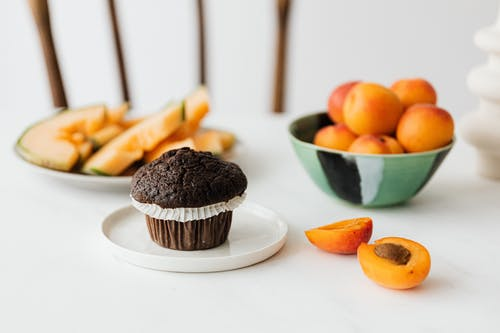 Halved ripe apricot near chocolate cupcake and assorted fruits on background
