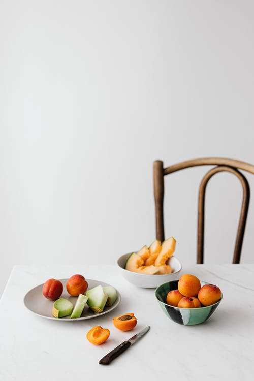Plate and bowl of delicious fruits with knife placed on white table near chair