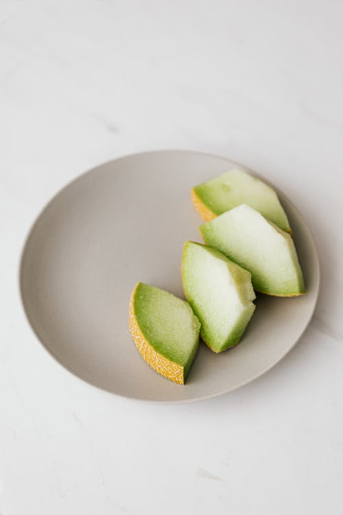 Slices of melon in plate placed on table