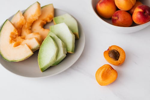 Fresh fruits in bowl and plate on table