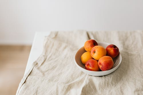 Bunch of ripe apricots in bowl placed on creasy tablecloth on white table