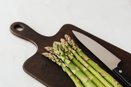 Knife and asparagus on wooden board