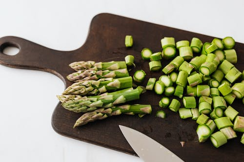 Bunch of asparagus and knife on cutting board