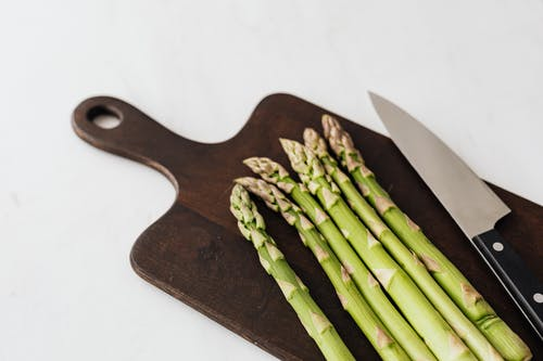 From above of green asparagus placed near kitchen knife on wooden cutting board on white table
