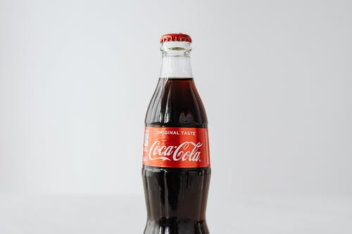 Closed bottle of coke on white background