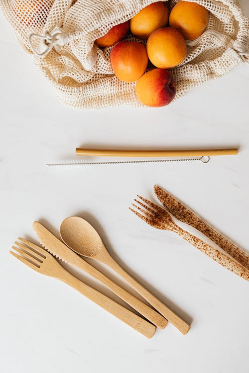 Cotton sack with ripe peaches and diverse cutlery on table