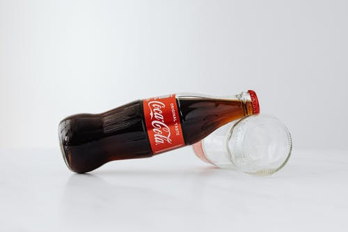 Closed bottle of soft drink leaned on empty bottle lying on white reflective surface