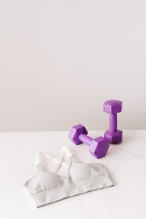 Purple dumbbells and white sport bra on table