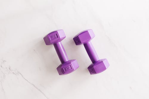 Purple all cast dumbbells on marble surface