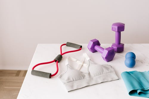 Set of sports equipment and bra for training placed on marble table