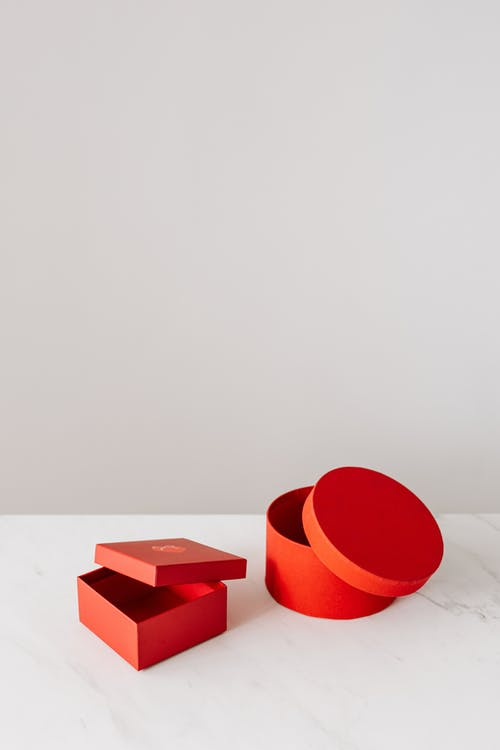 From above of empty square and round form red gift boxes with dislodged lid placed on white marble table against gray background