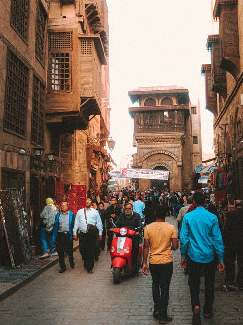 Medieval stone buildings along street full of tourists and local citizens in Egypt