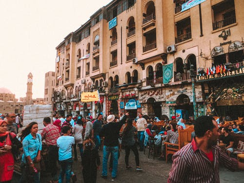 Crowded street of old city with people walking and resting in outdoor cafe
