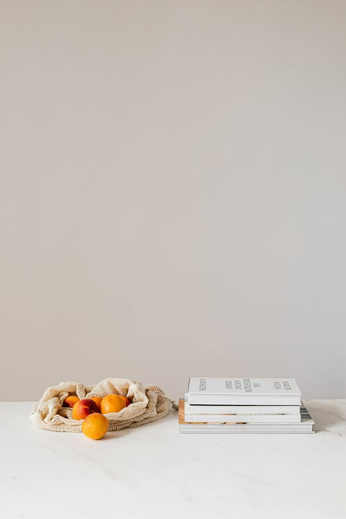 Composition of canvas bag with fresh ripe apricots placed on white table near stack of various books