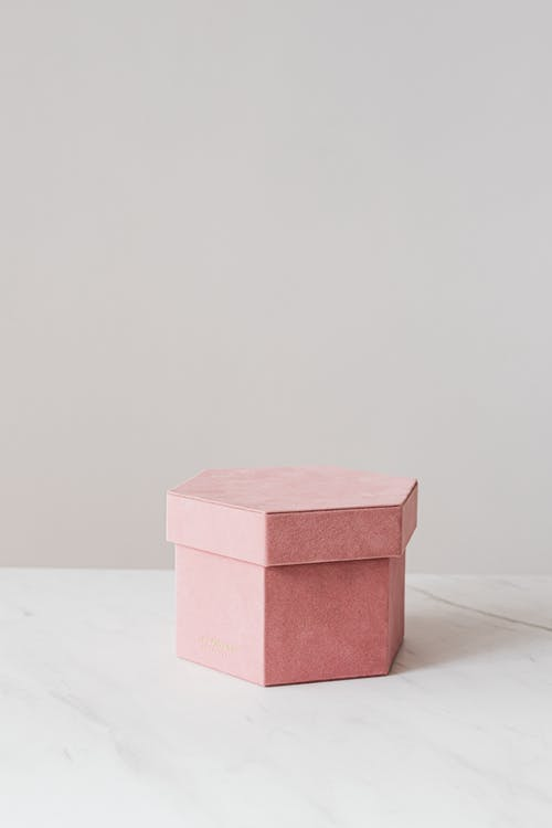 High angle of pink hexagon shaped gift box placed on white table against gray wall
