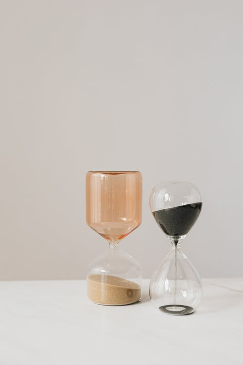 Amber and transparent hourglasses with rose and black sand placed on white table