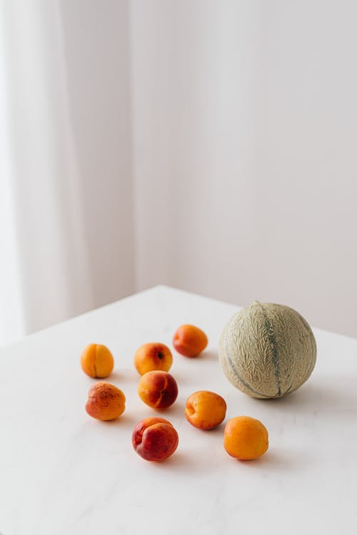From above composition of whole melon and ripe colorful apricots placed on white table