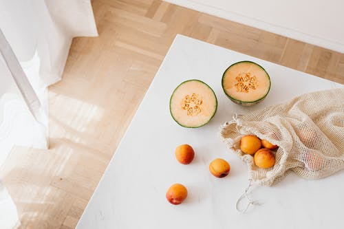 White table with halved melon and cotton sack with ripe apricots