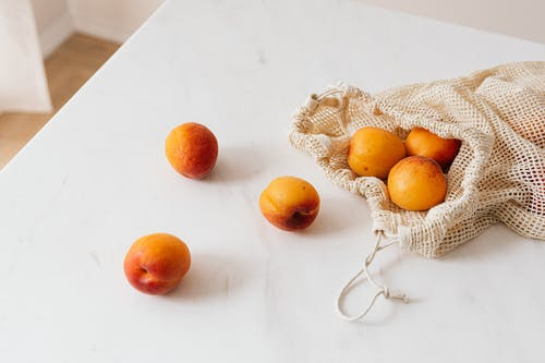 Organic sweet apricots in cotton sack placed on table