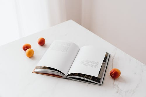 Opened book on table with fresh apricots