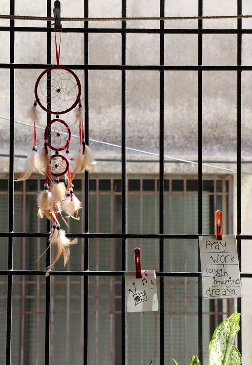 Metal bars on window decorated with hanging paper notes and dream catcher