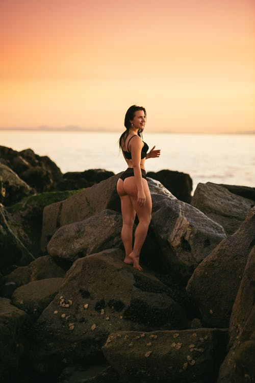 Fit woman standing on rocky seashore