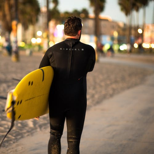 Unrecognizable man with surfboard on beach