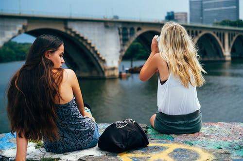 Back view of unrecognizable females wearing casual clothes sitting on border of embankment against bridge and enjoying weekend together