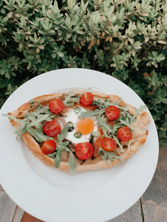 From above of khachapuri Georgian national product stuffed with cheese and eggs and garnished with arugula leaves and tomatoes
