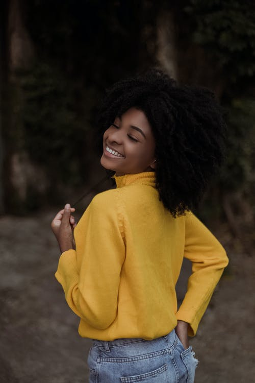 Woman in Yellow Sweater Standing on Dirt Ground