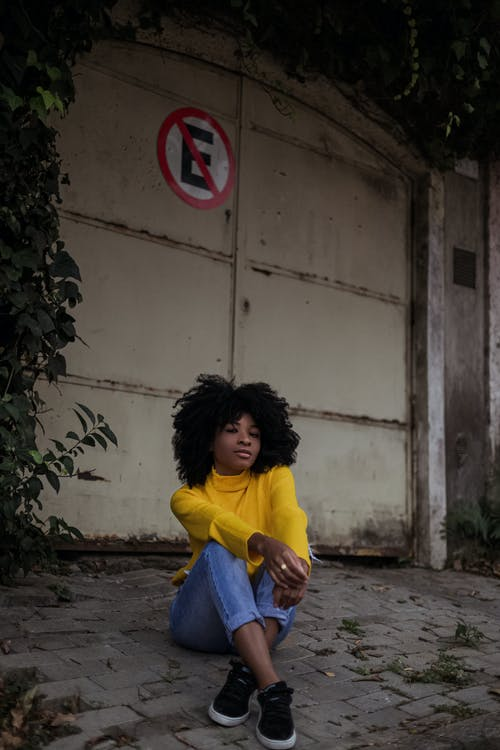 Woman in Yellow Shirt and Blue Denim Jeans Sitting on Concrete Bench