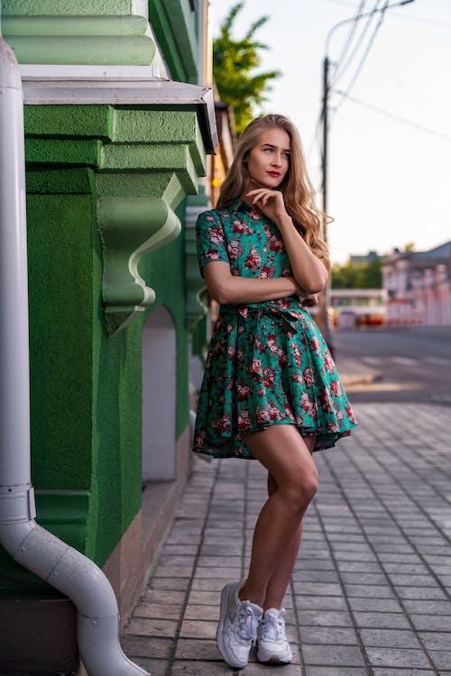 Stylish woman standing on sidewalk of street