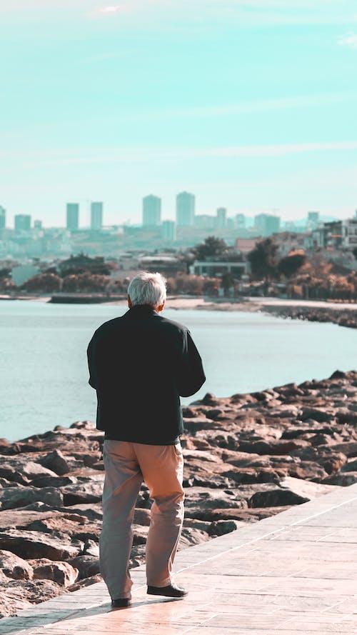 Unrecognizable man walking along embankment