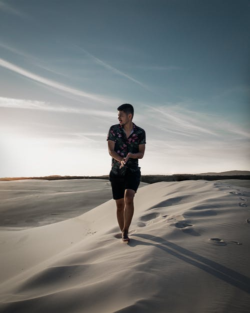 Woman in Black Shorts Standing on Brown Sand Under Blue Sky