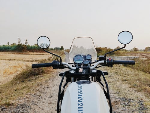 Motorcycle parked on walkway among field