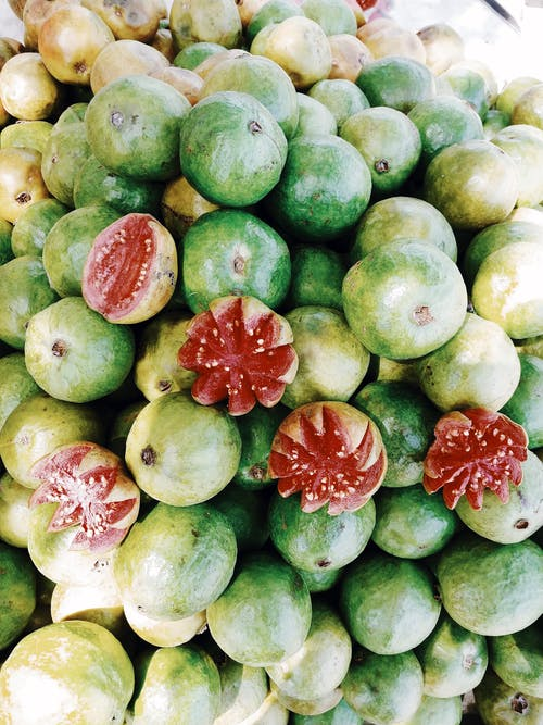 Top view of ripe guava fruits piled together and sold on street market
