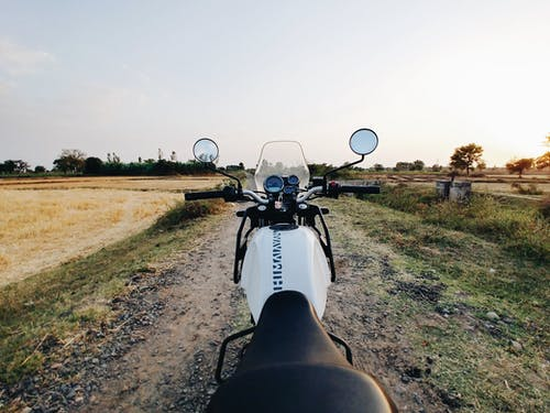 Motorbike parked on dirty pathway near rural field in evening during bright sunset