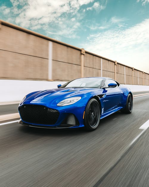 Contemporary powerful sports car of blue color moving fast along asphalt racetrack in daylight